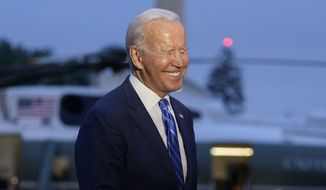 President Joe Biden laughs as he talks with reporters after returning to the White House in Washington, Tuesday, Oct. 5, 2021, after a trip to Michigan to promote his infrastructure plan. (AP Photo/Susan Walsh)
