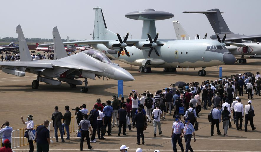 Visitors view the Chinese military's J-16D electronic warfare airplane, left, and the KJ-500 airborne early warning and control aircraft at right during 13th China International Aviation and Aerospace Exhibition, also known as Airshow China 2021, Wednesday, Sept. 29, 2021, in Zhuhai in southern China's Guangdong province. With record numbers of military flights near Taiwan over the last week, China has been stepping up its harassment of the island it claims as its own, showing a new intensity and sophistication as it asserts its territorial claims in the region. (AP Photo/Ng Han Guan) ** FILE **