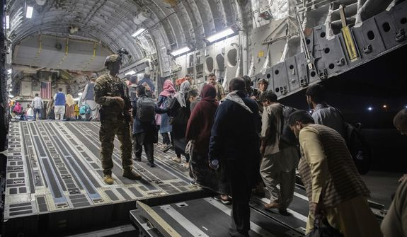 In this Aug. 22, 2021, file photo provided by the U.S. Air Force, Afghan passengers board a U.S. Air Force C-17 Globemaster III during the Afghanistan evacuation at Hamid Karzai International Airport in Kabul, Afghanistan. An Afghan man who worked for the U.S. government in Afghanistan says the Biden administration has ignored his pleas for help to evacuate his two young sons from Afghanistan after their mother died of a heart attack while being threatened by the Taliban. The International Refugee Assistance Project on Thursday, Oct. 7, 2021, filed a lawsuit against Secretary of State Antony Bilken on the man's behalf. The father fears for his children's safety and asked that he be identified only by his first name, Mohammad. (MSgt. Donald R. Allen/U.S. Air Force via AP) **FILE**