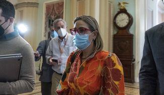 Sen. Kyrsten Sinema, D-Ariz., walks from a policy luncheon on Capitol Hill, Thursday, Oct. 7, 2021, in Washington. (AP Photo/Alex Brandon)