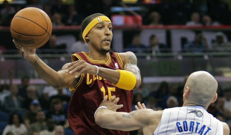 Cleveland Cavaliers' Jamario Moon, left, makes a pass over the head of Orlando Magic's Marcin Gortat (13), of Poland, during the first half of an NBA basketball game in Orlando, Fla., in this Friday, Nov. 26, 2010, file photo. Eighteen former NBA players, including Moon, have been arrested on charges alleging they defrauded the league's health and welfare benefit plan out of about $4 million, according to an indictment Thursday, Oct. 7, 2021. (AP Photo/John Raoux, File)