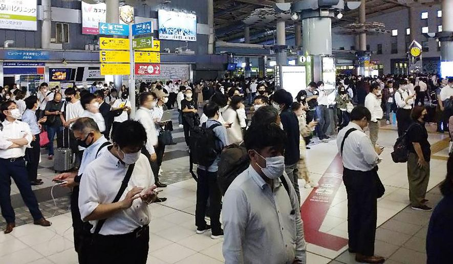Passengers are seen outside the entrance of JR Shinagawa station as the railway company makes safety check following an earthquake, in Tokyo, Thursday, Oct. 7, 2021. A powerful earthquake shook the Tokyo area on Thursday night, but officials said there was no danger of a tsunami.(Kyodo News via AP)
