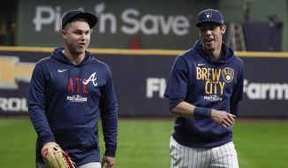 Milwaukee Brewers' Christian Yelich talks to Atlanta Braves' Joc Pederson at a practice for the Game 1 of the NLDS baseball game Thursday, Oct. 7, 2021, in Milwaukee. The Braves plays the Milwaukee Brewers in Game 1 on Friday, Oct. 8, 2021. (AP Photo/Morry Gash) **FILE**