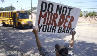 David Trujillo holds a sign as a school bus drives by on the street in front of a building housing an abortion provider in Dallas, Thursday, Oct. 7, 2021. A federal judge has ordered Texas to suspend a new law that has banned most abortions in the state since September. The order Wednesday by U.S. District Judge Robert Pitman freezes for now the strict abortion law known as Senate Bill 8. (AP Photo/LM Otero) **FILE**