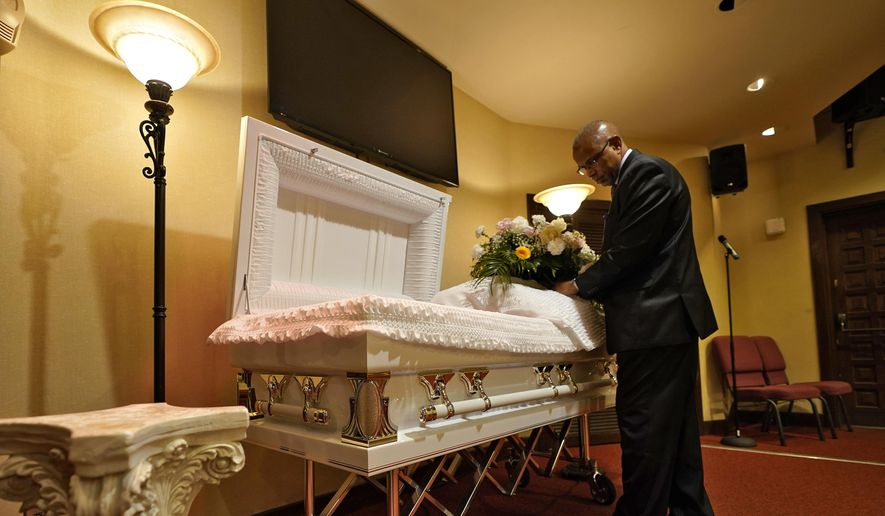 In this Thursday, Sept. 2, 2021, file photo, a funeral director arranges flowers on a casket before a service in Tampa, Fla. According to a study published Thursday, Oct. 7, 2021, by the medical journal Pediatrics, the number of U.S. children orphaned during the COVID-19 pandemic may be larger than previously estimated, and the toll has been far greater among Black and Hispanic Americans. (AP Photo/Chris O'Meara, File)