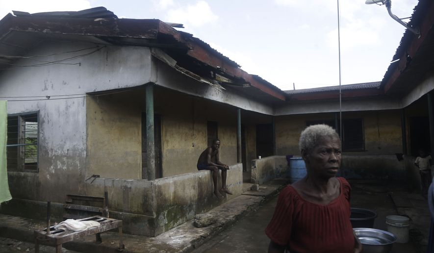 Christiana Eluozu stands outside her house with a damaged roof that she claims was damaged as a result of gas flare belonging to the Agip Oil company in Idu, Niger Delta area of Nigeria, Friday, Oct. 8, 2021. (AP Photo/Sunday Alamba)