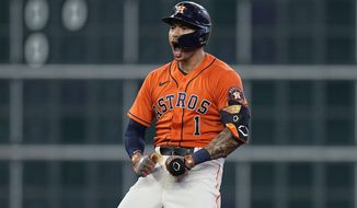 Houston Astros shortstop Carlos Correa (1) celebrates after hitting a two-run double against the Chicago White Sox during the seventh inning in Game 2 of a baseball American League Division Series Friday, Oct. 8, 2021, in Houston. (AP Photo/David J. Phillip)