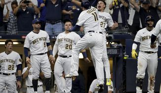 Milwaukee Brewers' Rowdy Tellez celebrates a two-run home run with Willy Adames during the seventh inning in Game 1 of baseball's National League Divisional Series against the Atlanta Braves Friday, Oct. 8, 2021, in Milwaukee.(AP Photo/Aaron Gash)