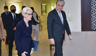 In this photo released by Pakistan's Ministry of Foreign Affairs, visiting U.S. Deputy Secretary of State Wendy Sherman, left, and Pakistan's Foreign Minister Shah Mahmood Qureshi, right, walk towards a meeting room at the Ministry of Foreign Affairs in Islamabad, Pakistan, Friday, Oct. 8, 2021. Sherman was meeting senior Pakistani officials Friday amid a worsening relationship between the two countries as each tries to navigate a way forward in Afghanistan under Taliban rule. (Ministry of Foreign Affairs vis AP)