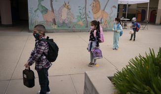 In this April 13, 2021, photo, socially distanced kindergarten students wait for their parents to pick them up on the first day of in-person learning at Maurice Sendak Elementary School in Los Angeles. The number of Americans getting COVID-19 vaccine shots is nearing an average of 1 million per day. Demand is expected to spike in a few weeks when elementary school-age children can begin getting vaccinated. (AP Photo/Jae C. Hong) **FILE**