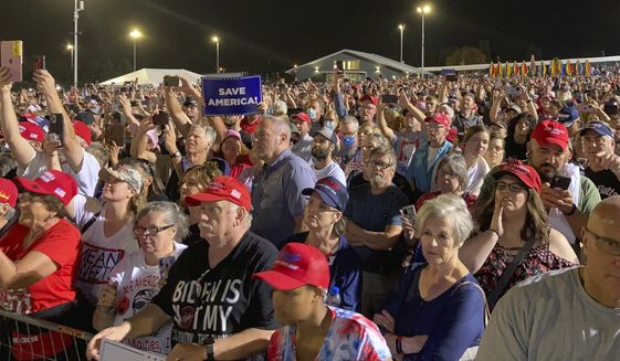 People wait for a rally with former President Donald Trump to begin at the Iowa State Fairgrounds in Des Moines, Iowa., Saturday, Oct. 9, 2021. (AP Photo/Thomas Beaumont)