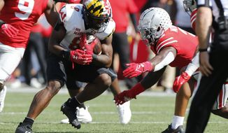 Ohio State linebacker Teradja Mitchell, right, tackles Maryland running back Tayon Fleet-Davis during the first half of an NCAA college football game Saturday, Oct. 9, 2021, in Columbus, Ohio. (AP Photo/Jay LaPrete)