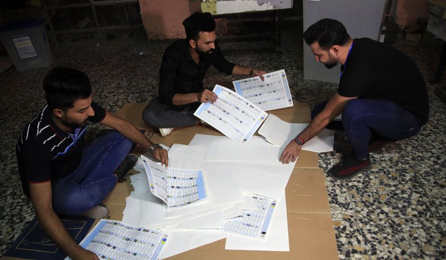 Election officials count ballots after polls close, at a polling station in Baghdad, Iraq, Sunday, Oct. 10, 2021. Iraq closed its airspace and land border crossings on Sunday as voters headed to the polls to elect a parliament that many hope will deliver much needed reforms after decades of conflict and mismanagement. (AP Photo/Hadi Mizban)