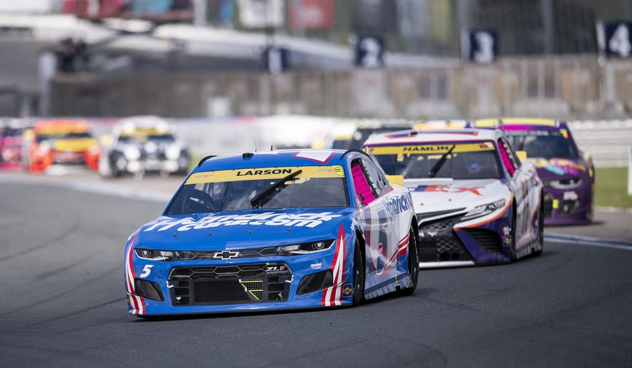 Kyle Larson (5) leads a pack of cars during a NASCAR Cup Series auto racing race at Charlotte Motor Speedway, Sunday, Oct. 10, 2021, in Concord, N.C. (AP Photo/Matt Kelley)