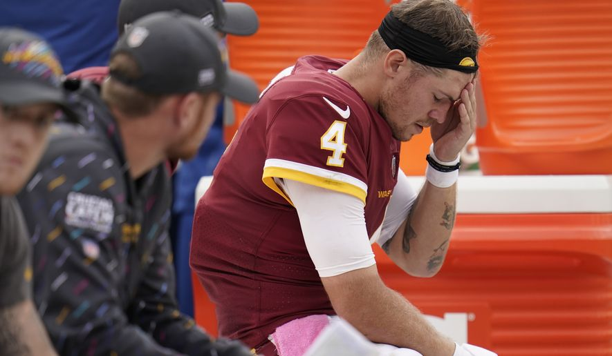 Washington Football Team quarterback Taylor Heinicke sits on the bench in the second half of an NFL football game against the New Orleans Saints, Sunday, Oct. 10, 2021, in Landover, Md. (AP Photo/Julio Cortez)