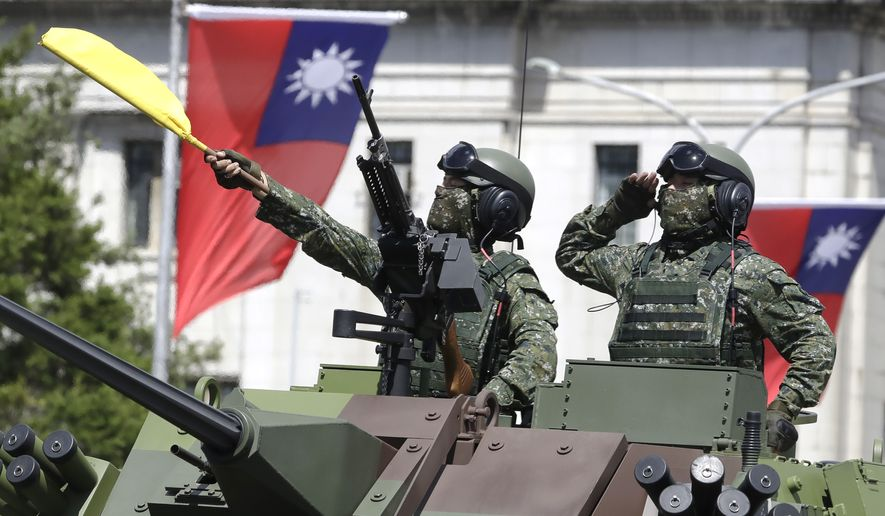 Taiwanese soldiers salute during National Day celebrations in front of the Presidential Building in Taipei, Taiwan, Sunday, Oct. 10, 2021. (AP Photo/Chiang Ying-ying)