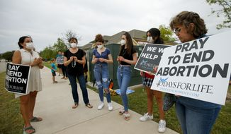 In this Friday, Oct. 1, 2021, photo, anti-abortion demonstrators pray and protest outside of a Whole Women's Health of North Texas, in McKinney, Texas. Foes of the strict abortion ban passed in Texas are taking aim at companies that donated money to the bill's sponsors, hoping consumers will pressure corporate America to join the fight against a surge of abortion restrictions. (AP Photo/Brandon Wade) **FILE**