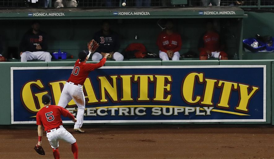 Boston Red Sox right fielder Hunter Renfroe (10) reaches for the ball, hit by Tampa Bay Rays Kevin Kiermaier, as it bounces over the wall after bouncing off Renfroe for a ground rule double during the thirteenth inning during Game 3 of a baseball American League Division Series, Sunday, Oct. 10, 2021, in Boston. (AP Photo/Michael Dwyer)