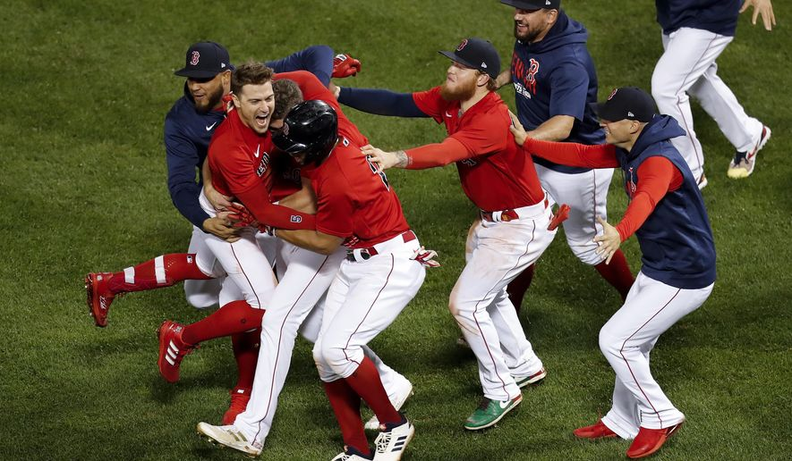 The Boston Red Sox celebrate after beating the Tampa Bay Rays on a sacrifice fly ball by Enrique Hernandez (5) during the ninth inning during Game 4 of a baseball American League Division Series, Monday, Oct. 11, 2021, in Boston. The Red Sox won 6-5. (AP Photo/Michael Dwyer)