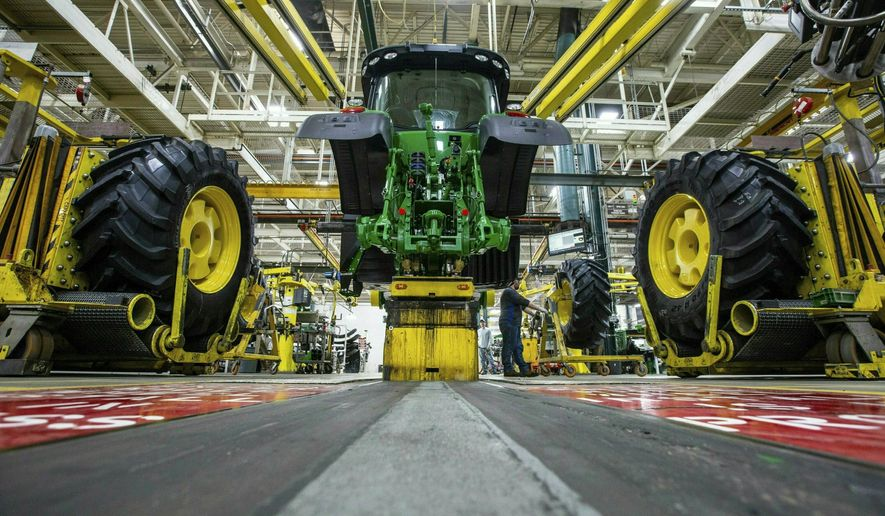 In this April 9, 2019, file photo, wheels are attach as workers assemble a tractor at the John Deere's Waterloo, Iowa, assembly plant. The vast majority of United Auto Workers union members rejected a contract offer from Deere & Co. Sunday, Oct. 10, 2021, that would have delivered at least 5% raises to the workers who make John Deere tractors and other equipment. (Zach Boyden-Holmes/Telegraph Herald via AP, File)