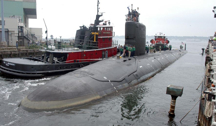 In this Friday, July 30, 2004, file photo, the U.S.S. Virginia returns to the Electric Boat Shipyard in Groton Conn., after its first sea trials. A Navy nuclear engineer with access to military secrets has been charged with trying to pass information about the design of American nuclear-powered submarines to someone he thought was a representative of a foreign government but who turned out to be an undercover FBI agent, the Justice Department said Sunday, Oct. 10, 2021. (AP Photo/Jack Sauer, File)
