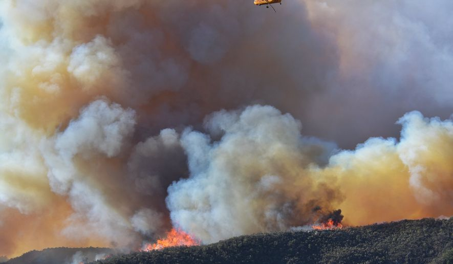 In this photo provided by Santa Barbara County Fire Department, a Croman Corp. Sikorsky SH-3 heads back to refill its tank to make another water drop as the Alisal Fire continues to burn in Refugio Canyon on Tuesday morning, Oct. 12, 2021,  in Santa Barbara County, Calif.  (Mike Eliason/Santa Barbara County Fire via AP)