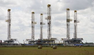 Drilling rigs stand idle Wednesday, June 30, 2021, in Calumet, Okla., as Oklahoma's drilling for new gas and oil wells is down from recent years. (AP Photo/Sue Ogrocki)