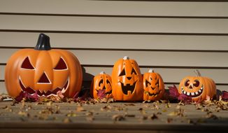 A display of Halloween pumpkins sits on the front porch of a home Thursday, Oct. 7, 2021, in Garretson, S.D. (AP Photo/David Zalubowski) ** FILE **