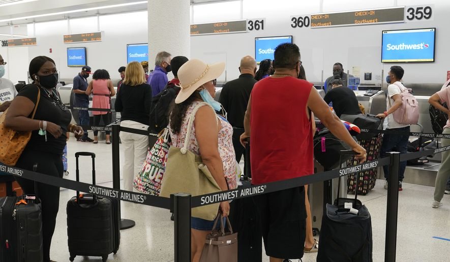 Southwest passengers wait to check in at Miami International Airport, Tuesday, Oct. 12, 2021, in Miami. Southwest Airlines appears to be fixing problems that caused the cancellation of nearly 2,400 flights over the previous three days. By midday Tuesday, Southwest had canceled fewer than 100 flights, although more than 400 others were running late. (AP Photo/Marta Lavandier)
