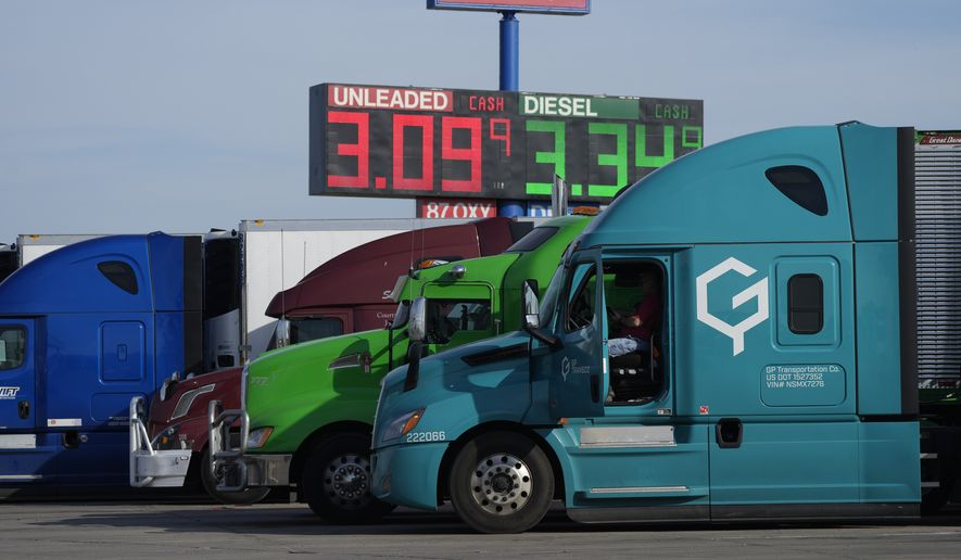 Cost of gasoline and diesel is displayed on an electronic sign hanging over a line of long-haul trucks parked at a stop off Interstate 90 Friday, Oct. 8, 2021, in Mitchell, S.D. (AP Photo/David Zalubowski)