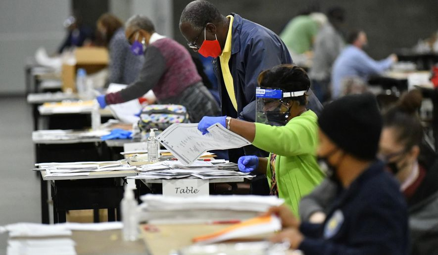 In this Saturday, Nov. 14, 2020, file photo, election workers in Fulton County began working through a recount of ballots in Atlanta. Investigators with Georgia's secretary of state's office have not found any evidence to substantiate claims that fraudulent or counterfeit ballots were counted in Fulton County during the 2020 general election. Henry County Superior Court Chief Judge Brian Amero is presiding over a lawsuit that alleges fraud in Fulton County during last year's election. (Hyosub Shin/Atlanta Journal-Constitution via AP, File)