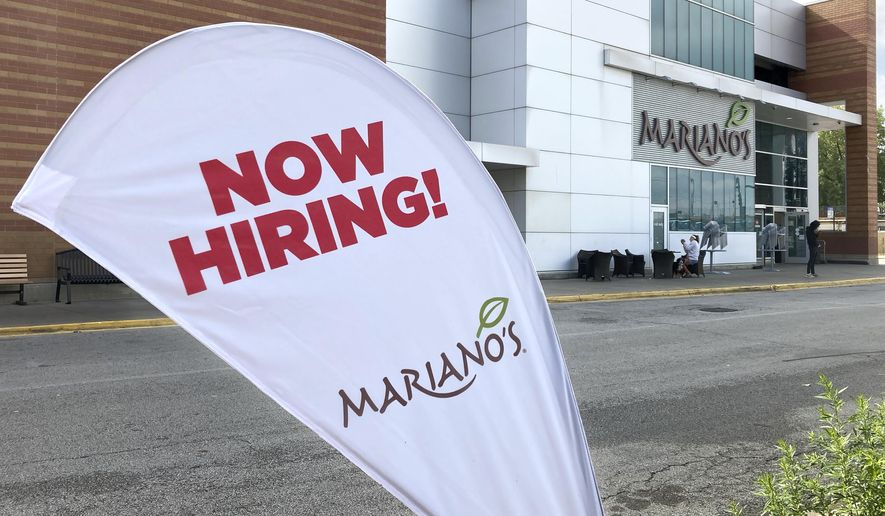 A sign in the parking lot of Mariano's grocery store advertises the availability of jobs Friday, Oct. 8, 2021, in Chicago.  One reason America's employers are having trouble filling jobs was starkly illustrated in a report Tuesday, Oct. 12: Americans are quitting in droves.  (AP Photo/Charles Rex Arbogast)