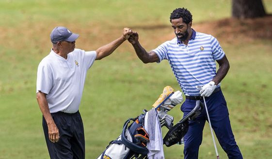 North Carolina A&T head golf coach Richard Watkins, left, bumps fists with and North Carolina A&T's J.R. Smith on the ninth hole during the second round of the Phoenix Invitational golf tournament in Burlington, N.C., Tuesday, Oct. 12, 2021. Smith spent 16 years playing in the NBA, winning two world championships. (Woody Marshall/News & Record via AP) **FILE**