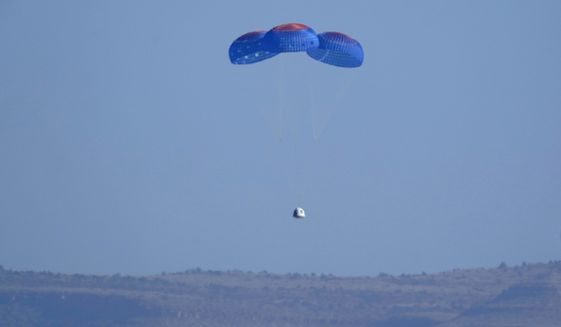 Parachutes carry the Blue Origin capsule with passengers William Shatner, Chris Boshuizen, Audrey Powers and Glen de Vries down to the spaceport near Van Horn, Texas, Wednesday, Oct. 13, 2021. (AP Photo/LM Otero)