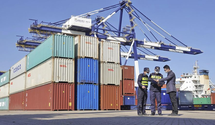 Custom officials check documents with a man at a container port in Yantai in eastern China's Shandong province Tuesday, Oct. 12, 2021. China's import and export growth slowed in September amid shipping bottlenecks and other disruptions combined with coronavirus outbreaks. (Chinatopix via AP)