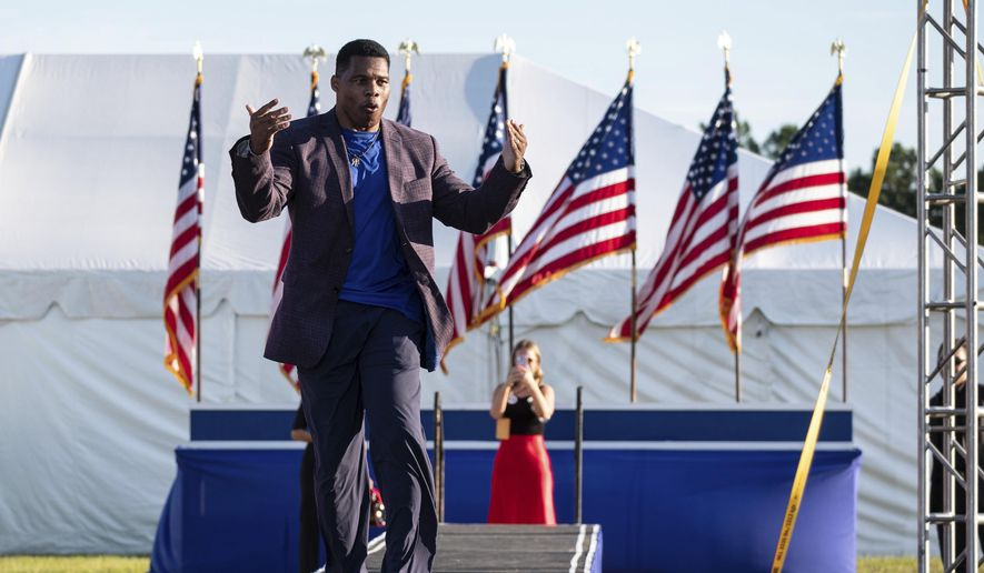 Senate candidate Herschel Walker takes the stage during former President Donald Trump's Save America rally in Perry, Ga., on Saturday, Sept. 25, 2021. Walker canceled a planned Texas fundraiser on Wednesday, Oct. 13, because an organizer was displaying a swastika made from syringes on social medial to protest mandatory vaccinations. (AP Photo/Ben Gray, File)