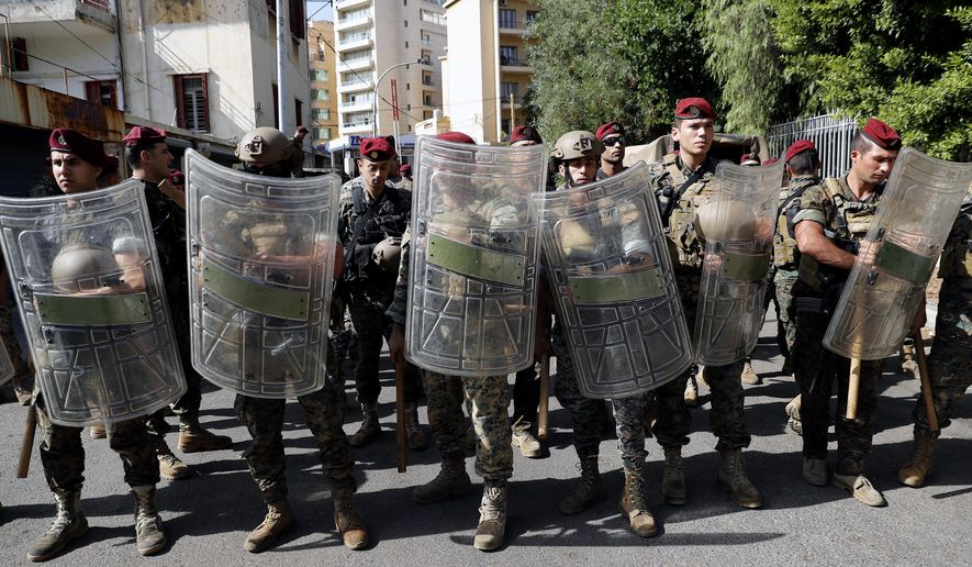 Lebanese army stand guard near the Justice Palace as supporters of the Shiite Hezbollah and Amal groups protest against Judge Tarek Bitar who is investigating last year's deadly seaport blast, in Beirut, Lebanon, Thursday, Oct. 14, 2021. (AP Photo/Hussein Malla)