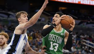 Boston Celtics' Enes Kanter (13) attempts a shot against Orlando Magic's Franz Wagner, left, during the second half of an NBA preseason basketball game, Wednesday, Oct. 13, 2021, in Orlando, Fla. (AP Photo/John Raoux)