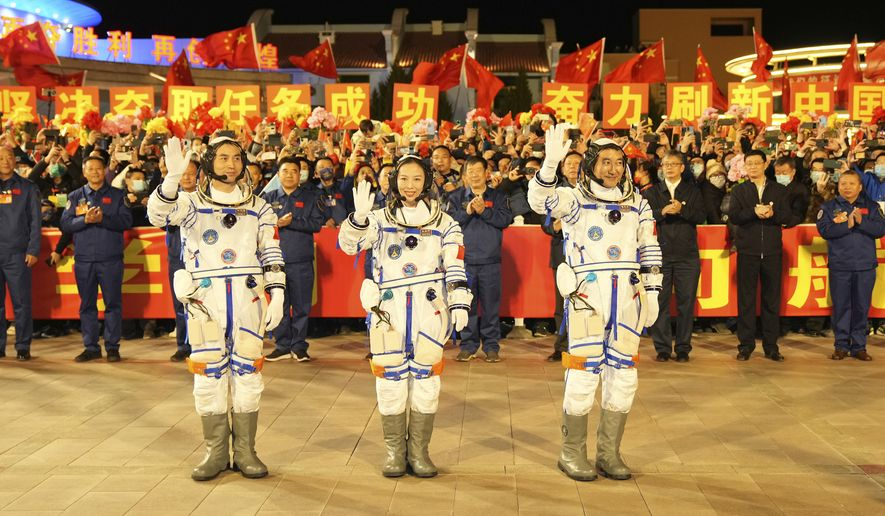 In this photo released by Xinhua News Agency, Chinese astronauts from left, Ye Guangfu, Wang Yaping and Zhai Zhigang wave before leaving for their Shenzhou-13 crewed space mission at the Jiuquan Satellite Launch Center in northwest China, Oct. 15, 2021. Shortly ahead of sending a new three-person crew to its space station, China on Friday renewed its commitment to international cooperation in the peaceful use of space. (Li Gang/Xinhua via AP)