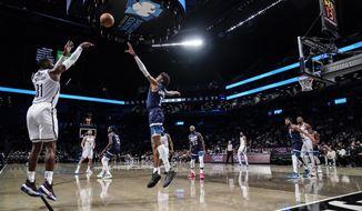 Brooklyn Nets' Paul Millsap (31) shoots a 3-pointer over Minnesota Timberwolves' Jaden McDaniels (3) during the second half of a preseason NBA basketball game Thursday, Oct. 14, 2021, in New York. (AP Photo/Frank Franklin II)
