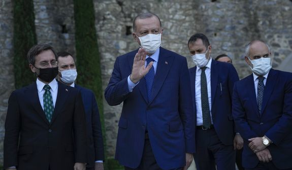 Turkey's President Recep Tayyip Erdogan, center, gestures to the media as he leaves after his meeting with German Chancellor Angela Merkel at Huber Villa presidential palace, in Istanbul, Turkey, Saturday, Oct. 16, 2021. The leaders discussed Ankara's relationship with Germany and the European Union as well as regional issues including Syria and Afghanistan. (AP Photo/Francisco Seco)