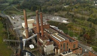 Smokestacks from the Greenridge Generation power plant tower above nearby homes, Friday, Oct. 15, 2021, in Dresden, N.Y. One Bitcoin mining operation in central New York came up with a novel solution in finding cheap energy to run the power-gobbling computer arrays that create and transact cryptocurrency: It took over Greenidge Generation which now produces about 44 megawatts to run 15,300 computer servers, plus additional electricity it sends into the state's power grid. (AP Photo/Julie Jacobson)