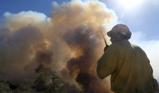 FILE - In this Oct. 13, 2021, file photo, a firefighter watches as smoke rises from a wildfire in Goleta, Calif. Fire crews made significant progress overnight against the wildfire burning for nearly a week in the Southern California coastal mountains, officials said Sunday, Oct. 17. (AP Photo/Ringo H.W. Chiu, File)