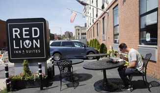In this Aug. 25, 2016, file photo, New York Mets minor league pitcher Gary Cornish, of the Mets Class A New York-Penn League Brooklyn Cyclones, eats his habitual breakfast in the parking lot of the Red Lion Inn & Suites in New York where he and the other members of his team stay when the team is not traveling. Major League Baseball says its owners have agreed to begin providing housing to certain minor league players beginning in the 2022 season. ESPN, citing anonymous sources, first reported Sunday, Oct. 17, 2021, on the owners decision, saying the league would require teams to provide housing either via stipends to fully cover housing or by arranging the lodging themselves. (AP Photo/Kathy Willens, File) **FILE**