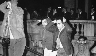 """FILE - In this Oct.17, 1967 file photo, Algerians come out of Paris subway station with their hands on their heads after being arrested in Paris for failure to obey curfew imposed on Algerians. A tribute march is organized in Paris Sunday Oct.17, 2021 for the 60th anniversary of the bloody police crackdown on a protest by Algerians in the French capital, during the final year of their country's independence war with the colonial power. About 12,000 Algerians were arrested and """"several dozens"""" were killed, """"their bodies thrown into the Seine River."""" Historians say at least 120 protesters have been killed, some shot and some drowned in the Seine River. (AP Photo, File)"""
