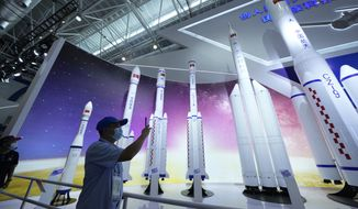 In this Sept. 29, 2021, file photo, a visitor takes photos of replicas of space launch rockets Airshow China 2021 in Zhuhai, southern China's Guangdong province. China said Monday its launch of a new spacecraft was merely a test to see whether the vehicle could be re-used. (AP Photo/Ng Han Guan, File)