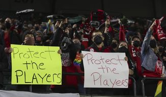 Portland Thorns fans hold signs during the first half of the team's NWSL soccer match against the Houston Dash in Portland, Ore., Wednesday, Oct. 6, 2021. Players stopped on the field in the first half of Wednesday night's National Women's Soccer League games and linked arms in a circle to demonstrate solidarity with two former players who came forward with allegations of sexual harassment and misconduct against a prominent coach. (AP Photo/Steve Dipaola) **FILE**