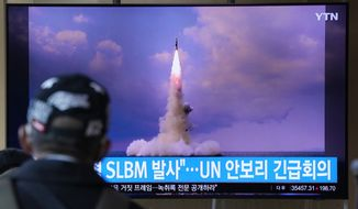 """A man watches a TV screen showing an image of North Korea's ballistic missile launched from a submarine during a news program at Seoul Railway Station in Seoul, South Korea, Wednesday, Oct. 20, 2021. North Korea announced Wednesday that it had tested a newly developed missile designed to be launched from a submarine, the first such weapons test in two years and one it says will bolster its military's underwater operational capability. Korean letters read: """"North Korea launched a Submarine-Launched Ballistic Missile and U.N. security council emergency meeting."""" (AP Photo/Ahn Young-joon)"""
