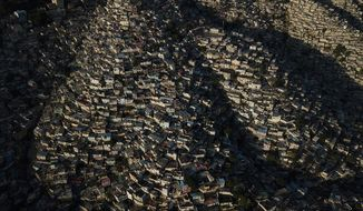Homes stand densely packed in the Jalouise neighborhood of Port-au-Prince at sunrise, Tuesday, Oct. 19, 2021. (AP Photo/Matias Delacroix)