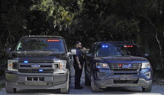 North Port, Fla., police officers block the entrance to the Myakkahatchee Creek Environmental Park Wednesday, Oct. 20, 2021, in North Port, Fla. Items believed to belong to Brian Laundrie and potential human remains were found in a Florida wilderness park during a search for clues in the slaying of Gabby Petito . (AP Photo/Chris O'Meara)